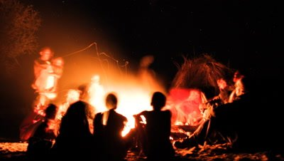 Medium wide angle tribal people San bushmen gathered around a campfire in the bush with big sky and stars