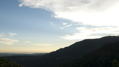 Wide angle sunset behind foreground mountains with distant river flood plain