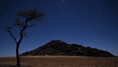 Wide angle rocky desert landscape with starry sky as moon sets behind rise
