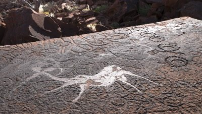 Close up on rock face as shadows move across rock and light lifts revealing ancient rock engraving of The Dancing Kudu
