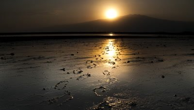 Wide angle sun rises over footprints in mud by side of lake then burns out