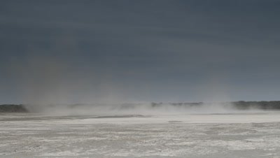 Wide angle clouds of dust blowing across white salt pan with blue sky overhead