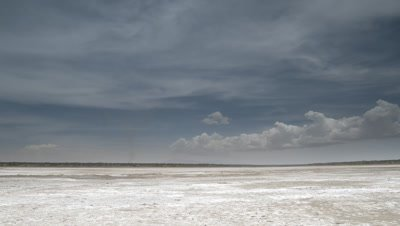 Big wide angle salt pan with dramatic racing rain clouds overhead releasing their rain on the parched earth