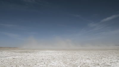 Wide angle dramatic clouds of dust blowing away across white salt pan with blue sky overhead