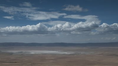 Big wide angle pan from Crater rim revealling extent of Ngorongoro Crater from marsh to salt pan with blue sky and white fluffy clouds