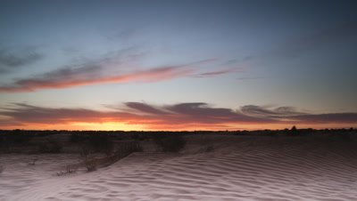 Wide angle sunrise from black over Saharan sand dunes then burns out