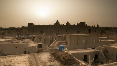 Medium wide angle sunrise over mud city rooftops featuring Djenne mosque, largest mud structure in world
