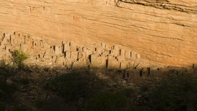 Wide angle top shot, shadow moves down cliff face to reveal Gogon cliff houses at bottom of escarpment