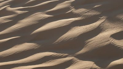 Close up pan over sand dune as shadow lifts to reveal pale gold ripple pattern