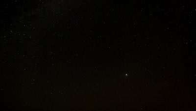 Wide angle black twinkly starry night sky moves overhead