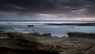 Wide angle rocky shoreline as dawn breaks with motion blur tide and racing storm clouds overhead pierced by sunlight