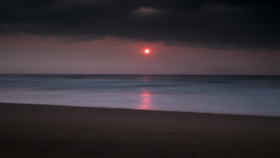 Wide angle soft pink mauve sunrise over sea with waves lapping the sand and red sun which rises up into dark cloud and disappears
