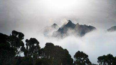 Medium wide angle clouds swirling around peaks of the Ruwenzori, concealing and revealing mountains then night falls