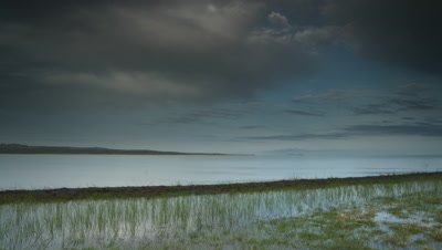 Wide angle Lake Turkana shoreline with pastel blue sky and soft white clouds;