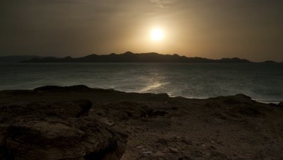 Wide angle rocky shore falling away to shimmering Lake Turkana as sun sets behind island in mid-distance