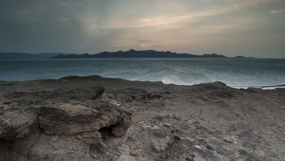 Wide angle rocky shore falling away to Lake Turkana at dusk looking towards islands in mid-distance as night falls