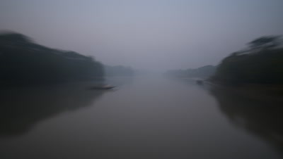 Medium wide angle point of view travelling along tropical, misty, tree lined river
