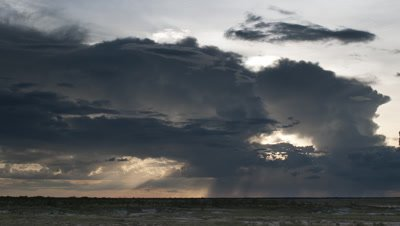 Wide angle dramatic dark rain clouds dropping showers of rain over Etosha salt scrub land as sun sets