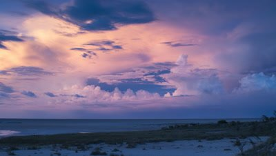 Wide angle pretty soft pink and blue evening clouds move over Etosha salt pan as night falls