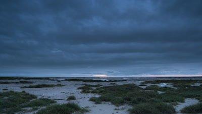 Wide angle cloudy grey dawn over Etosha salt pans, Namibia