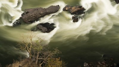 Mid top shot of Zambesi river with motion blur and black basalt rocks midstream, Batoka Gorge, downstream of Victoria Falls