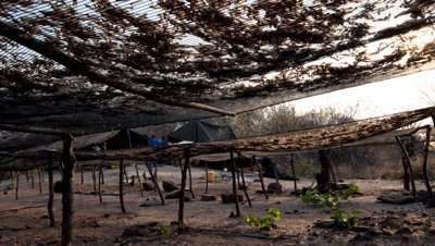 Medium wide angle shadows move across kapenta fish drying racks as people to and fro in Tonga village, Lake Kariba