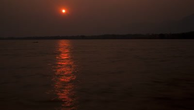 Wide angle orange sun sets over water