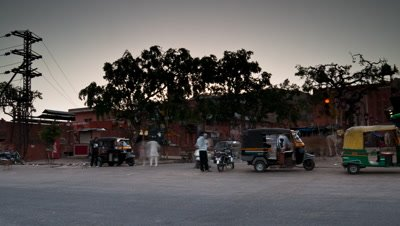 Medium wide angle pan as day gradually dawns, along busy road with constant traffic to roadside stalls with sun temple behind