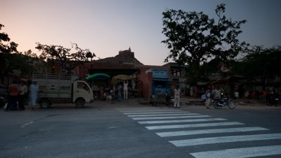 Medium wide angle pan at night then day gradually dawns, along busy road with constant traffic to rest on roadside stalls with sun temple behind