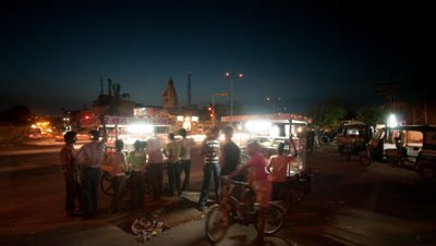 Medium wide angle two snack vendors with customers at main road intersection from evening through to night, Galta Junction