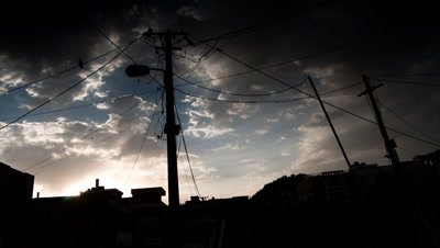 Medium wide angle electricity poles and wires silhouetted against sky as clouds move rapidly away behind