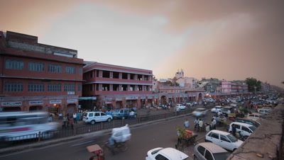 Medium wide angle busy Jaipur street with monsoon clouds overhead as evening becomes night