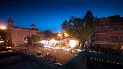 Medium wide angle traffic flowing through pink arch Jaipur city gate as evening becomes night