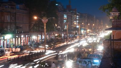 Medium wide angle busy Jaipur street with pink sandstone buildings at night