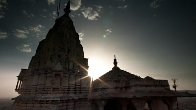 Mid shot Galta sun temple with sun glimpsing from behind roof and blue sky