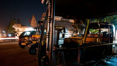 Mid shot stationary tuk tuks parked by side of busy road at night