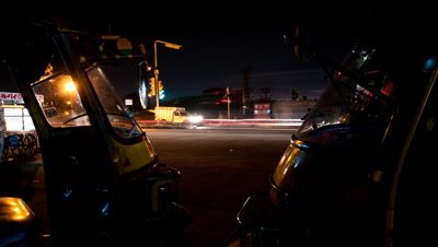 Medium wide angle tuk tuks parked in foreground with busy traffic intersection behind and motion blur lights at night