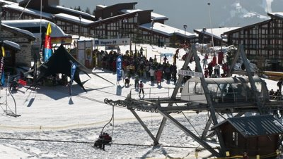 Medium wide angle chair lifts and queues at Arc 1800 ski resort in France