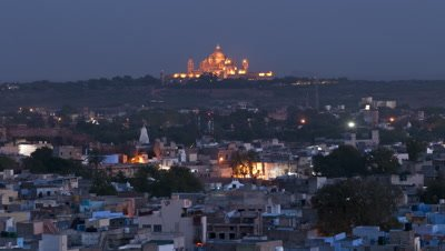 Wide angle Jodhpur city as night falls featuring the floodlit Umaid Bhawan Palace in background
