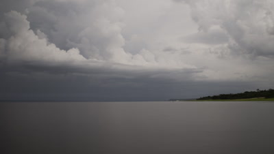 Wide angle grey cumulonimbus storm clouds discharge lightning over the Amazon River then darkens to black