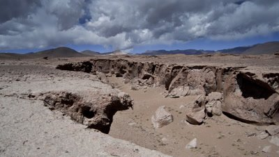 Wide angle vast dry sandy plateau with gathering storm clouds rolling overhead as camera tracks along edge of gorge
