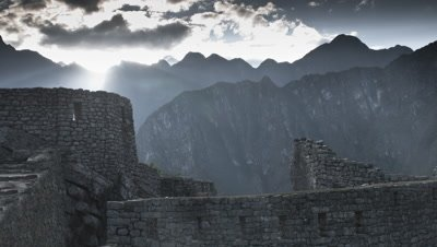 Wide angle buildings of Machu Picchu with mountains beyond as sun rises above peaks and god rays push through the clouds