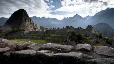 Wide angle Machu Picchu buildings foreground with majestic mountain peaks and clouds behind