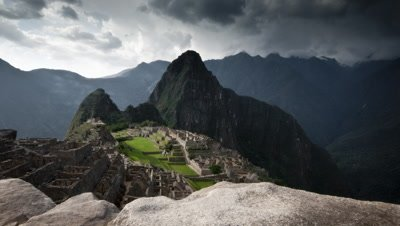 Wide angle tracking along stone parapet wall to reveal classic view down onto Machu Picchu with mountain backdrop