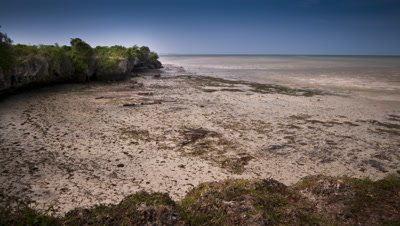 Medium wide angle crystal clear tropical sea with tide retreating from white sandy beach and brilliant blue sky
