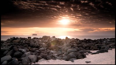 Sunset into sea over classic Galapagos rocky shoreline, South Saunders Island
