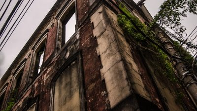 Pan shot of derelict building in Manaus with rain clouds building over.