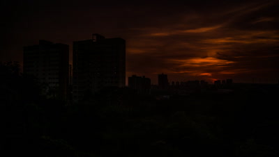 Sun rises over city apartment blocks emerging from forest with rain clouds