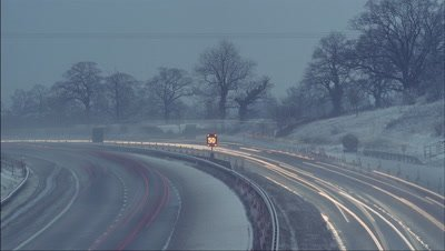 Medium wide angle from bridge looking down on motorway, light snowy conditions and busy traffic with pull in and out of focus to 50 mph speed sign