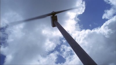 Low wide angle looking up at actively spinning wind turbine with blue sky, sun and clouds
